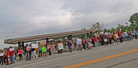 photo by Toby Weiss | QT scene on August 16, 2014 Michael Brown Peach March. To see it burn was heartbreaking. To have it become a people's park makes sense. It feels odd for a gas station to have such emotional impact. Every trip back to this area, the QT feels like a phantom limb. Considering the QT corporate model of closing old ones when a new mega-mart is built ( like further up W. Florissant) I personally don't see them rebuilding this location. Make it a memorial!